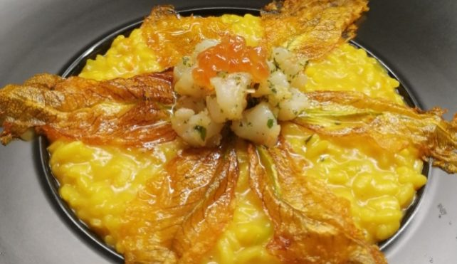 Risotto allo zafferano, fiori di zucca, gamberoni e uova di salmone
