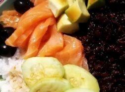 Poke bowl di riso bianco e nero, con salmone, avocado, cetrioli e olive